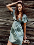 Sexy girl in green silk dress on a background of a wooden wall. Beautiful sexy young woman with long brown hair in evening makeup shiny silk or satin green dress Royalty Free Stock Photography