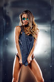Sexy girl on grey background. Very sexy girl in a fashion clothes and eyeglasses Stock Photography