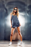 Sexy girl on grey background. Very sexy girl in a fashion clothes and eyeglasses Stock Photo