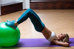 Sexy girl in a gym doing yoga on the ball Royalty Free Stock Photos