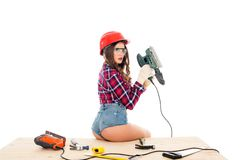 Girl in hardhat posing with grind tool on wooden table with tools,. Isolated on white royalty free stock photo