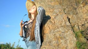 Girl in a hat and glasses. Near a stone at sunset royalty free stock photo