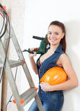 Sexy  girl in headphones with drill and hardhat Stock Photos