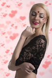 Sexy girl with heart shaped decoration smiles Stock Photography