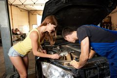 Sexy girl helps an auto mechanic repair car in garage. A sexy girl helps an auto mechanic repair a car in a garage. The girl is frankly dressed holding a Stock Photography