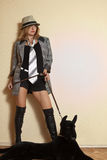Girl in high boots and hat posing in interior with dog on floor. Girl in high boots posing and hat in interior with dog lying on floor stock photo
