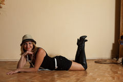 Sexy girl in high boots and hat posing in interior on floor Royalty Free Stock Images
