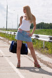 Sexy girl on highway. Sexy girl with a bag on highway Royalty Free Stock Photos