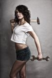 Sexy girl holding hammer and wrench spanner Royalty Free Stock Photos