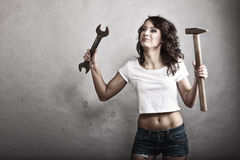 Sexy girl holding hammer and wrench spanner Royalty Free Stock Photography