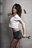 Sexy girl holding hammer and wrench spanner Royalty Free Stock Image