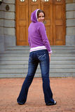 Girl in Jeans. Young woman, standing with her back to the camera, looking back at it, posing in a attitude stock photos