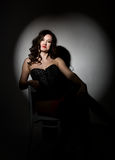 Sexy girl in lacy lingerie and corset, sitting on chair posing in the studio a dark background Stock Photography