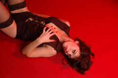 Sexy girl laying on red background. Sexy girl in black  undies on red background Stock Photos