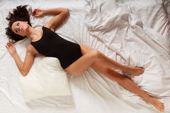 Sexy girl lazy woman with pillow on bed in bedroom Royalty Free Stock Photo