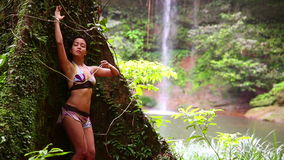 Sexy girl leaning huge tree in rainforest background waterfall stock video footage