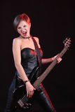 Sexy girl in leather clothes with bass guitar Royalty Free Stock Photography