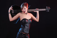 Sexy girl in leather clothes with bass guitar Royalty Free Stock Images