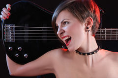 Sexy girl in leather clothes with bass guitar Royalty Free Stock Image