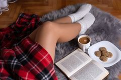 Sexy Girl Legs On A Cozy Carpet With White Socks And Covered With A Plaid Blanket. Girl Sitting At Home And Warming On A Winter Ni Stock Photos