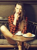 Girl licks finger. Girl pretty slim model in red checkered shirt and shorts licks finger on vintage coach in coffee cafe stock image