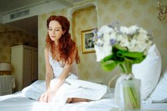 Beautiful sexy redhair lady in elegant white panties and peignoir. Fashion portrait of model indoors. Beauty woman with lace linge. Sexy girl lies on the bed Stock Photography