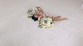 Portrait of a model girl with a snake in a Studio. A sexy girl lies on the floor among large bouquets of flowers and two snakes creep along it. Beautiful girl stock video footage