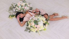 A sexy girl lies on the floor with two snakes. A sexy girl lies on the floor among large bouquets of flowers and two snakes creep along it. Beautiful girl holds stock footage