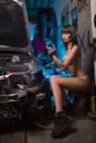 Sexy girl in lingerie car repairs Royalty Free Stock Image