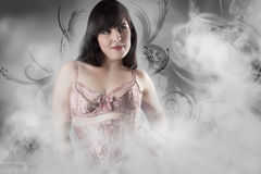 Sexy girl with lingerie over smoke backdrop Royalty Free Stock Photography