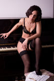 Sexy girl in lingerie about piano Stock Photos