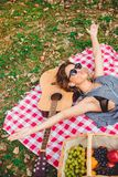 Girl listening music, pouting and spreading arms on a picnic royalty free stock image