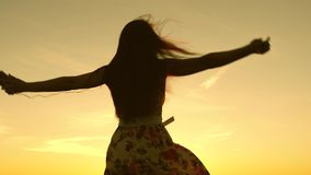 Sexy girl listening to music and dancing in rays of a beautiful sunset against the sky. young girl in headphones and. With a smartphone whirl in flight under stock video