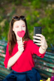 girl with a lollipop is taking a selfie Stock Image