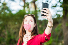 girl with a lollipop is taking a selfie Royalty Free Stock Image