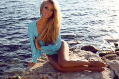 girl with long blond hair in fashion swimsuit relaxing on beach Stock Photo