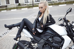 girl with long blond hair in leather jacket,posing on motorbike Royalty Free Stock Photography