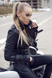 girl with long blond hair in leather jacket,posing on motorbike Stock Photos