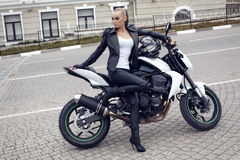 girl with long blond hair in leather jacket,posing on motorbike Stock Photography