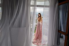Beautiful young girl model. Girl with long hair in amazing clothes posing in hotel royalty free stock photography