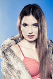 Sexy girl with long hair in red bra underwear and fur coat on blue Royalty Free Stock Photography