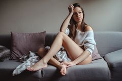 Sexy girl with long legs sitting on a sofa Royalty Free Stock Photography