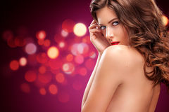 Girl with long and shiny wavy hair . Beautiful model, curly hairstyle on red background. St valentine`s day. Brunette girl with long and shiny wavy hair royalty free stock photography