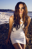 Sexy girl with long wet hair in elegant dress posing beside a sea Stock Photography