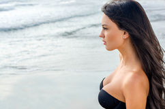 Sexy girl looking at the sea. Sexy girl with long brunette hair looking at the sea. Girl wearing a strapless top revealing a gorgeous cleavage Stock Photo