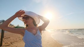 Sexy girl looking at the sea. A girl in a hat and glasses is looking for a look towards the ocean. One left, lost. Sexy girl looking at the sea. A girl in a hat stock footage