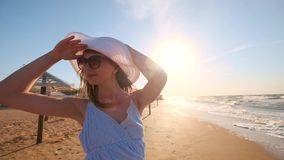 Sexy girl looking at the sea. A girl in a hat and glasses is looking for a look towards the ocean. One left, lost. Sexy girl looking at the sea. A girl in a hat stock video footage