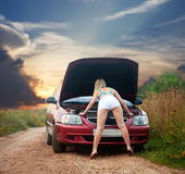 girl looking under the car hood Stock Photo