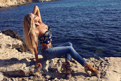 Sexy girl with luxurious blond hair in jeans posing on beach Royalty Free Stock Image