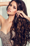 Sexy girl with luxurious curly dark hair in elegant beige dress Royalty Free Stock Images